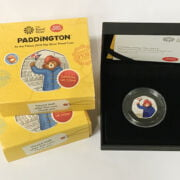 TWO 2018 FIFTY-PENCE SILVER PROOF COINS PADDINGTON BEAR AT THE PALACE & STATION, BOXED WITH COA