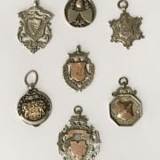 FOUR GOLD & SILVER BADGES & 3 SILVER BADGES